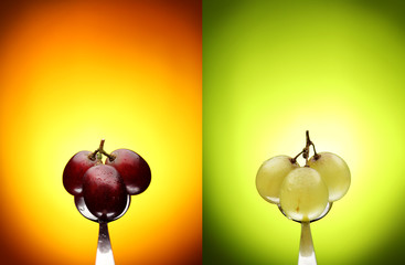 green and red grapes on a teaspoon and a colored background