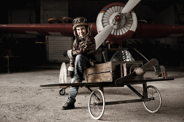 Young Aviator in a aircraft in a hangar with these planes