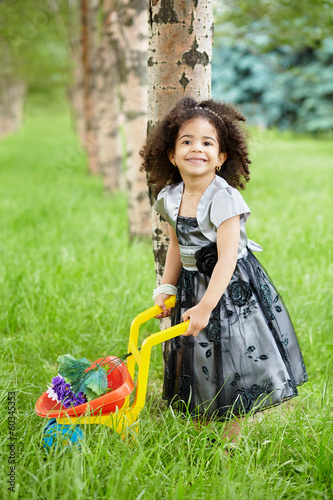 Smiling little girl dressed in beautiful black gown stands
