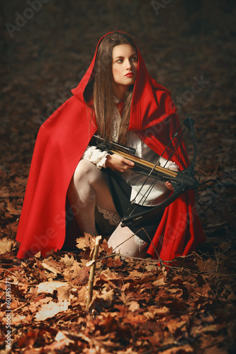 Fashion little red riding hood posing in the forest