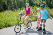 Mother rides bicycle and her children ride rollers on sunny day