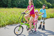 Mother and children ride bicycle and rollers on sunny day