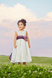 Little girl in beautiful gown stands on meadow