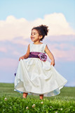 Little smiling mulatto girl in beautiful gown stands