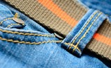 Blue jeans with orange belt, macro shot.