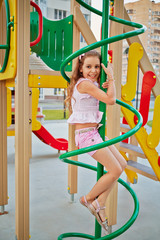 Little girl climbs a pole at children playground in house yard