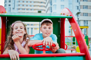 Boy and girl sit on car spring swing at children playground