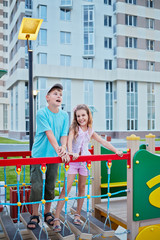 Boy and his younger sister play on children playground