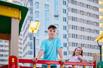 Boy and his younger sister having fun on children playground