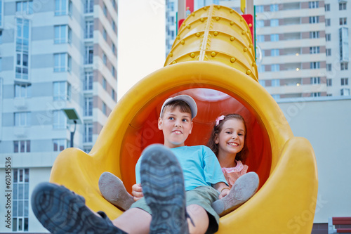 Boy and his younger sister sit at bottom of slide