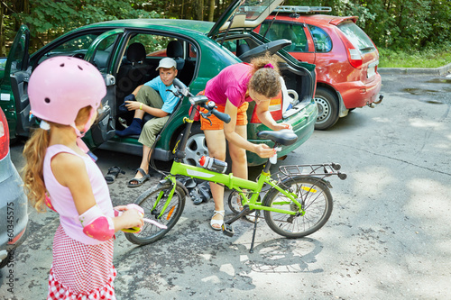 Family prepares to ride bicycle and rollers