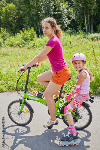 Mother rides bicycle and her daughter in rollers sits