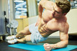 Man bodybuilder does exercise lying on one side