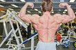 Bodybuilder poses in gym hall demonstrating tense muscles