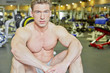 Bodybuilder sits on floor in gym hall taking rest