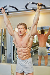 Bodybuilder prepares to do  lateral and abdominal exercises