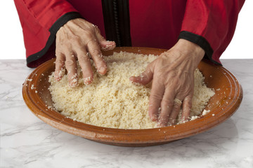 Hands making traditional Moroccan couscous