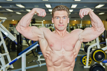 Bodybuilder poses demonstrating tense muscles in gym hall
