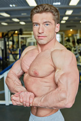Bodybuilder poses demonstrating muscles in gym hall