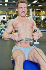 Bodybuilder trains on workout equipment in gym hall