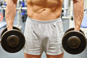 Muscular torso and hands with dumbells of man in gym hall