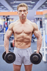 Bodybuilder stands with dumbbell in his hands in gym hall