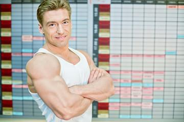 Half-length portrait of bodybuilder who stands half-turned