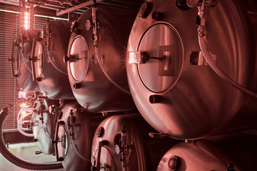 Horizontal tanks at brewery in red light