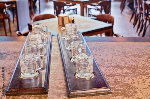 Two beer paddles with empty beer mugs on counter