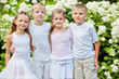 Children stand embraced against white blooming bushes