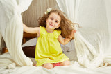 Smiling little girl in yellow dress sits on tent bed
