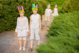 Boy and girl in stylized indian headdress stand on walkway