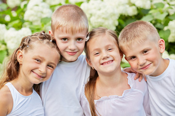 Portrait of four smiling children standing head to head