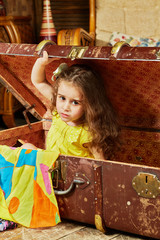 Little girl in yellow dress gets out from old suitcase