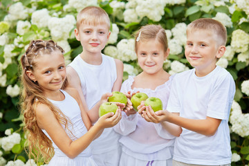 Smiling children hold green apples in folded palms