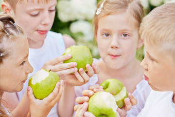 Closeup portrait of four children who eat green apples standing