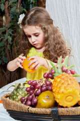 Little girl peels tangerin standing near basket full of fruits