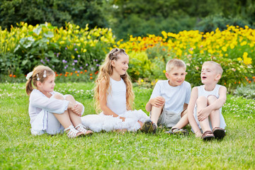 Four children sit on grass at loawn, one boy sings
