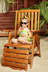 Little girl dressed in swimming suit and in dark sunglasses sits