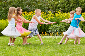 Two children teams play tug-of-war