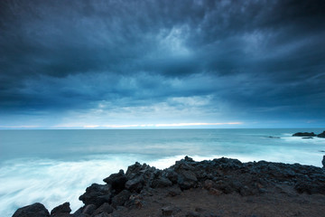 Dramatic sky over volcanic coast at dusk ( Lanzarote )
