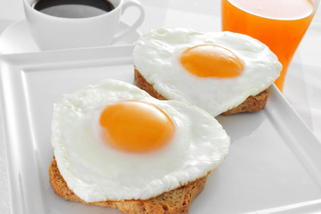 heart-shaped fried eggs, bread and orange juice