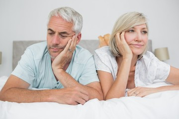 Close-up of displeased mature couple lying in bed