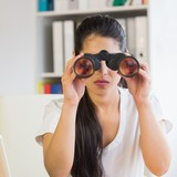 Determined businesswoman looking through binoculars