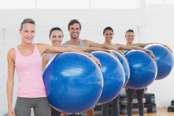 Fitness class holding exercise balls at fitness studio