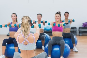 Class exercising with dumbbells on fitness balls