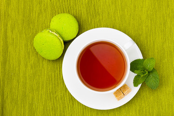 cup of tea and macarons on the green tablecloth