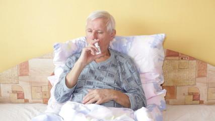 Sick senior man using nasal spray in bed.