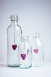 Three pink felted hearts in glass bottles