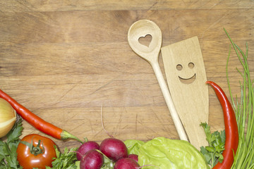 Vegetables and kitchenware on cutting board background concept